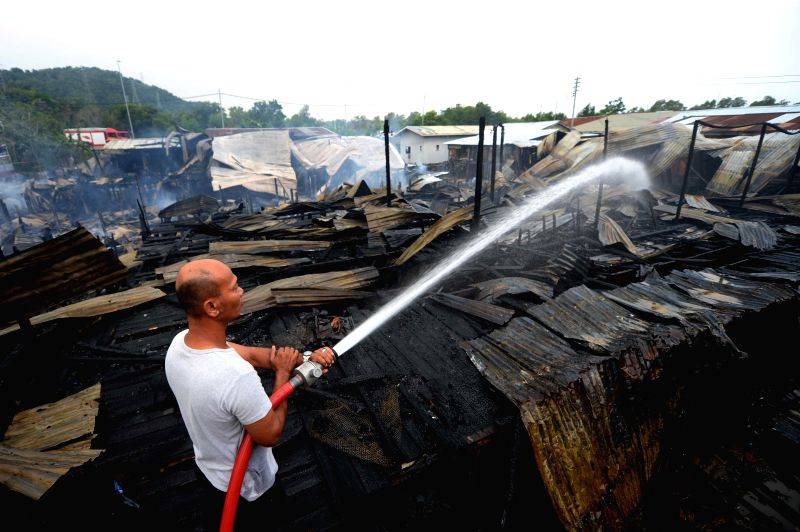 Photo taken on July 29, 2014 shows a man trying to put out the fire at an island some 40 km away from Kota Kinabalu, the capital of Sabah, Malaysia. One died, 200 ...