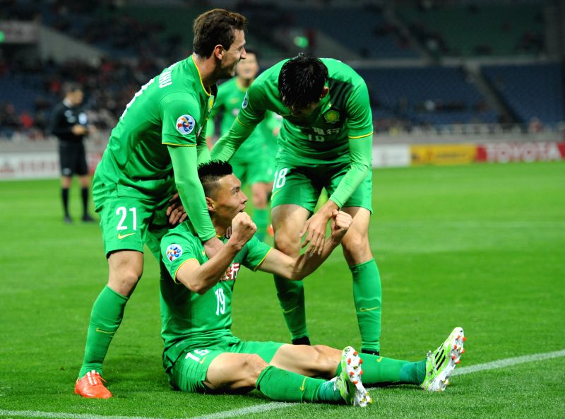 Yu Dabao (bottom) of China's Beijing Guoan reacts after scoring against Japan's Urawa Red Diamonds during their group E match at the 2015 AFC Champions League in ...