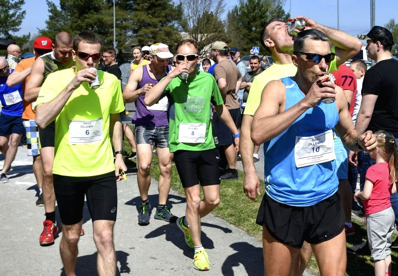 SAKU, May 21, 2017 - Participants drink beer during the Beer Mile Run in Saku, Estonia, May 20, 2017. Participants must run four laps for a total of one mile distance and start each lap by drinking a ...