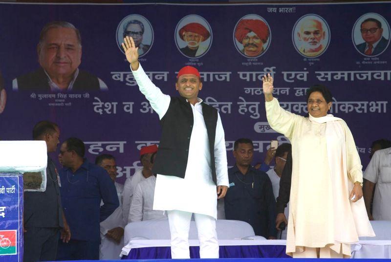 Salempur: Samajwadi Party President Akhilesh Yadav and Bahujan Samaj Party (BSP) chief Mayawati wave at supporters during SP-BSP-RLD's joint rally in Uttar Pradesh's Salempur, on May 14, 2019.