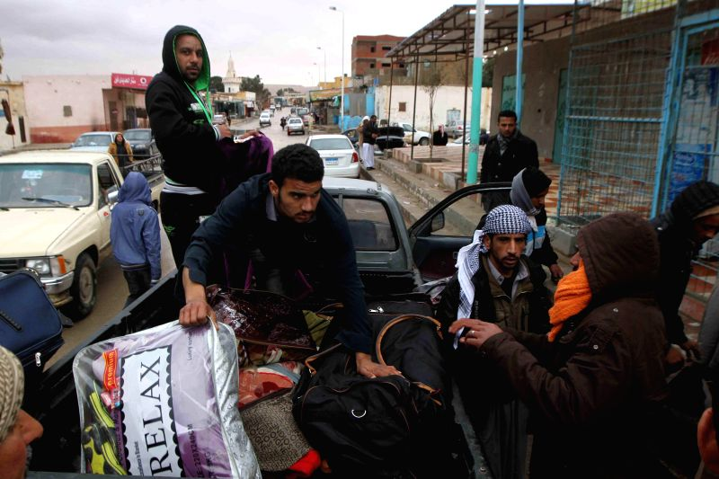 Egyptian men load their luggage as boarding a bus back home in Salloum, Egypt, east of the border with?Libya, on Feb. 19, 2015. Over 6,000 Egyptians have returned ...