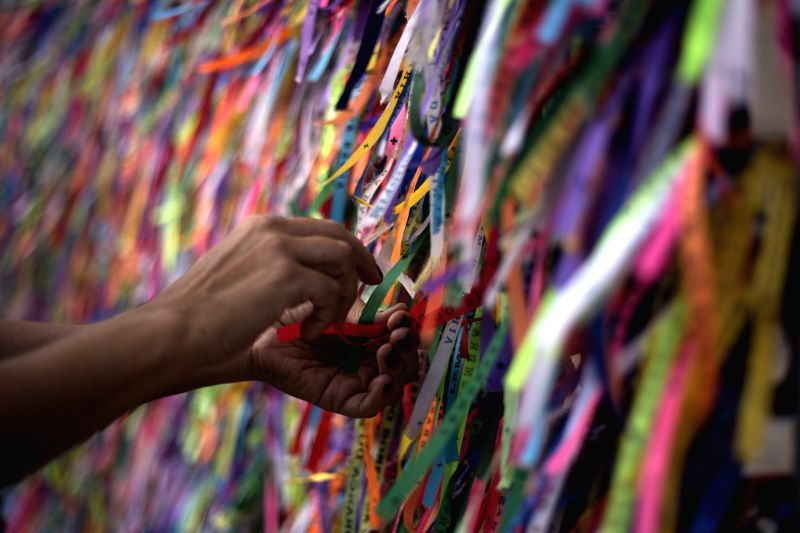 A woman ties a ribbon at the Senhor do Bonfim Church in Salvador, Brazil, July 6, 2014.  The traditional ribbons of the Senhor do Bonfim, are tied with knots in ...