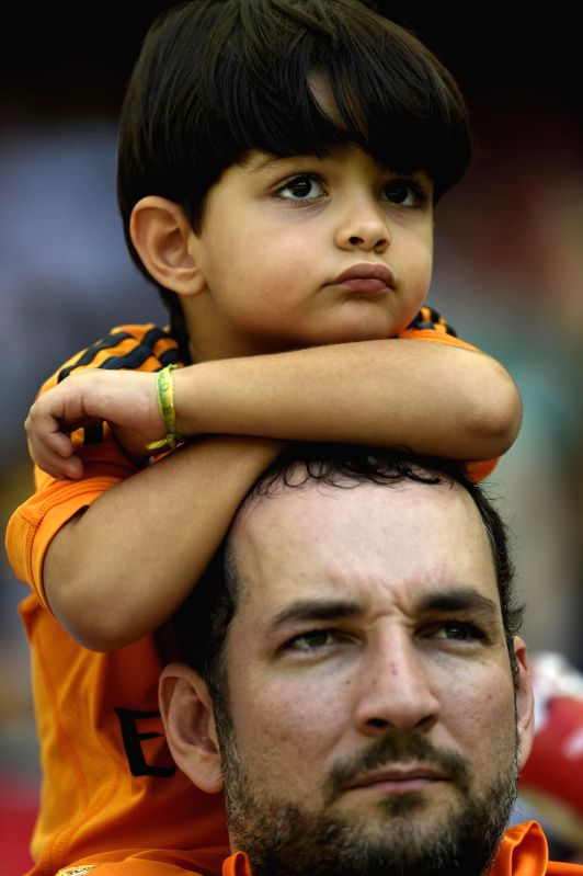 A man and his son look on prior to a Group G match between Germany and Portugal of 2014 FIFA World Cup at the Arena Fonte Nova Stadium in Salvador, Brazil, June ...