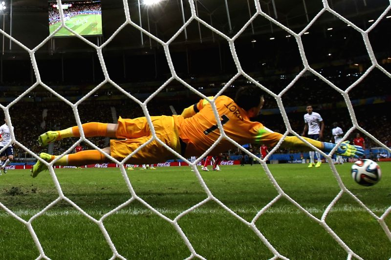 France's goalkeeper Hugo Lloris tries to block a shot during a Group E match between Switzerland and France of 2014 FIFA World Cup at the Arena Fonte Nova Stadium .