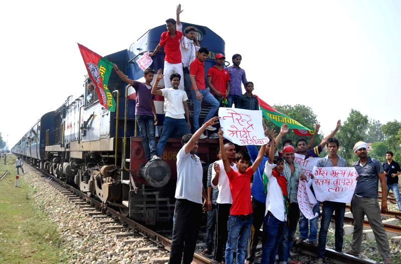Samajwadi Party workers demonstrate on railway tracks to protest against hike in fuel prices in Allahabad on July 2, 2014.