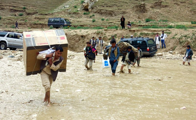 Afghans carry their goods from the flooded area after a heavy rain in Samanagan province, northern Afghanistan, May 12, 2015.
