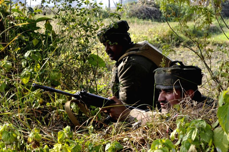 Soldiers take position during an encounter with militants who launched an attack on an army camp in Samba district of Jammu and Kashmir on March 20, 2015.