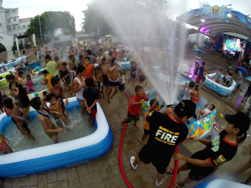 """Children play with water sprayed from a fire truck during the """"Wattah-Wattah Festival"""" in San Juan City, the Philippines, June 23, 2014. People are ."""