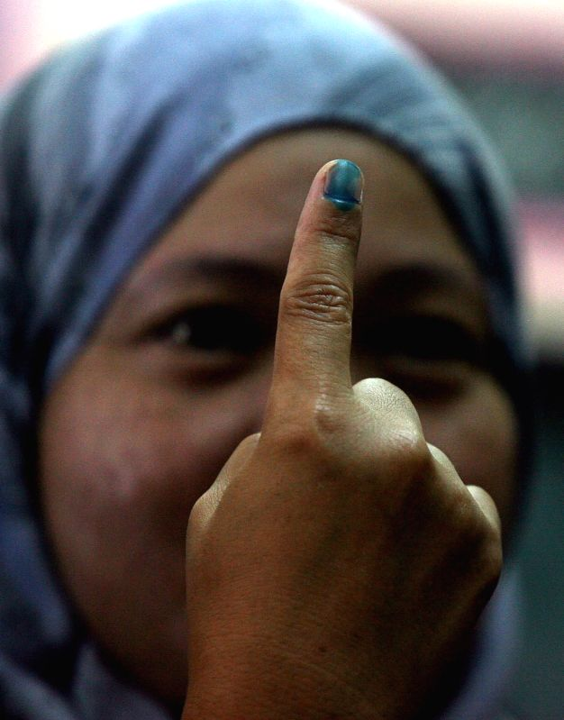 SAN JUAN CITY, May 9, 2016 - A Muslim woman shows ther index finger marked with indelible ink after casting her vote inside a school turned into a polling precinct in San Juan City, the Philippines, ...