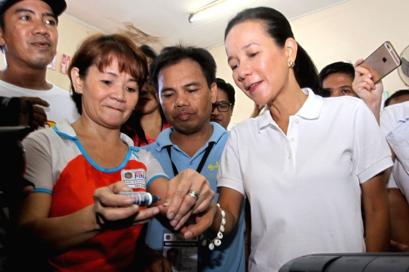 SAN JUAN CITY, May 9, 2016 - Presidential candidate Senator Grace Poe (R) has her index finger marked with indelible ink after casting her vote inside a classroom turned into a polling precinct at a ...
