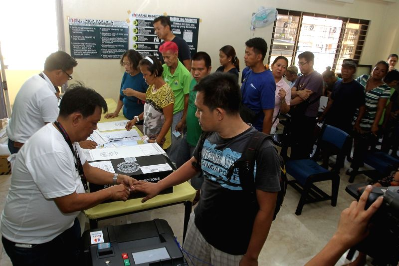 SAN JUAN CITY, May 9, 2016 - Voters line up to cast their ballots inside a school turned into a polling precinct in San Juan City, the Philippines, May 9, 2016. Millions of Filipinos began casting ...