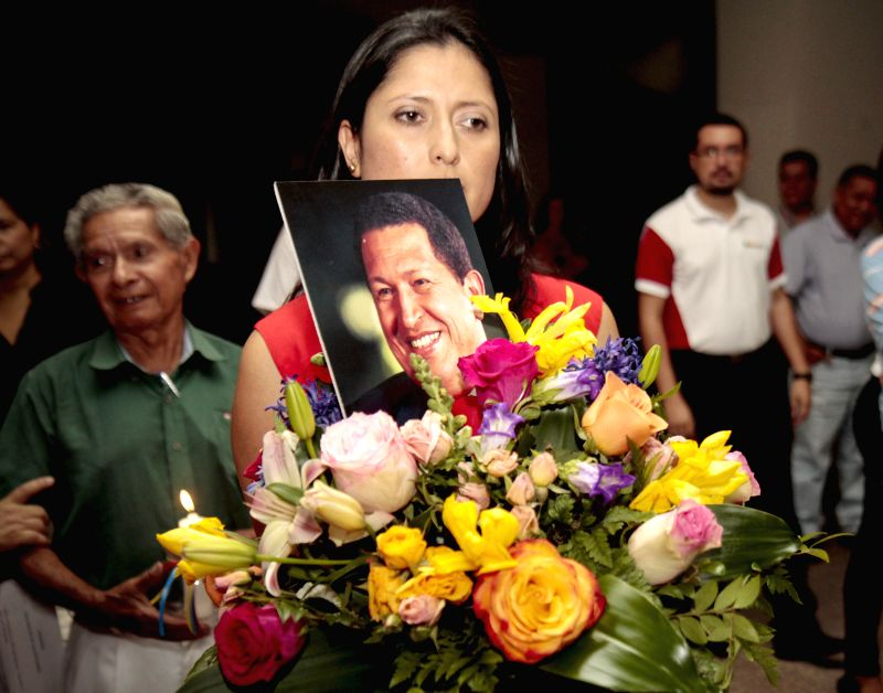 A Salvadoran woman holds a photography of late Venezuelan President Hugo Chavez, during a ceremony to mark the 2nd anniversary of his death, at Metropolitan ...