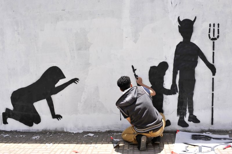 A Yemeni activist draws a graffiti to protest against recruitment of child soldiers, on a wall in Sanaa, Yemen, on April 10, 2014. The United Nations has a list of ..