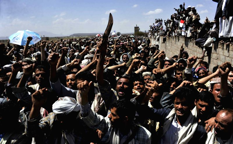Fighters of the Shiite Houthi group shout slogans during a rally demanding the resignation of Yemeni government at the Hamdan area, about 30 km north of the capital ..