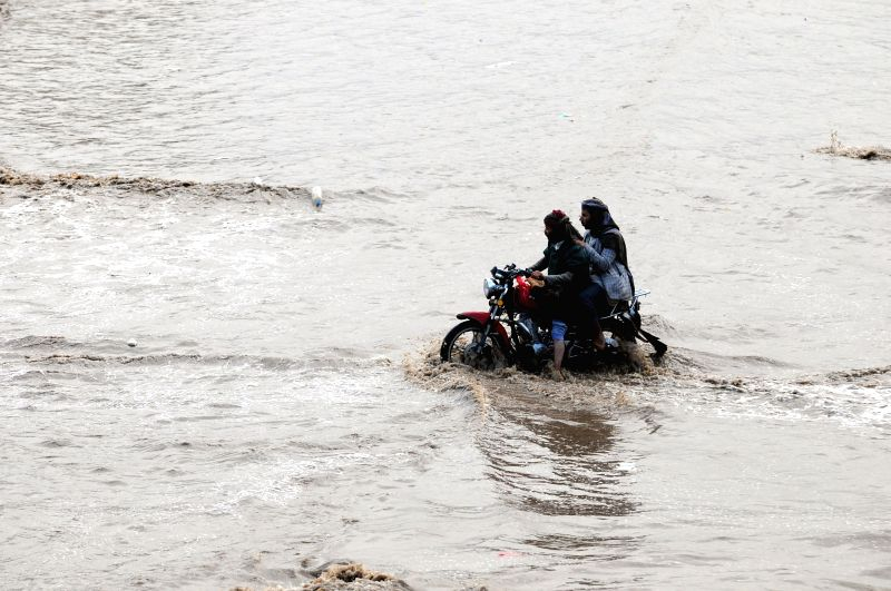 SANAA, Aug. 6, 2018 - People ride a motorcycle in a flooded area in Sanaa, Yemen, on Aug. 6, 2018. Heavy rain hit Sanaa on Monday afternoon, causing flooding and traffic disruption inside the city.