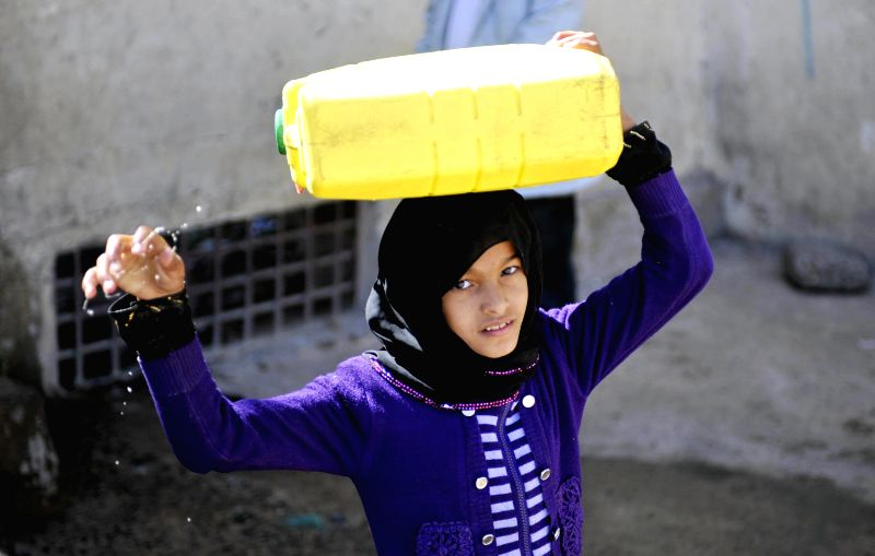 A girl carries water at a public water point in Sanaa, Yemen, on Dec. 17, 2014. Yemen is one of the Middle East countries with severe water shortage because of the ...