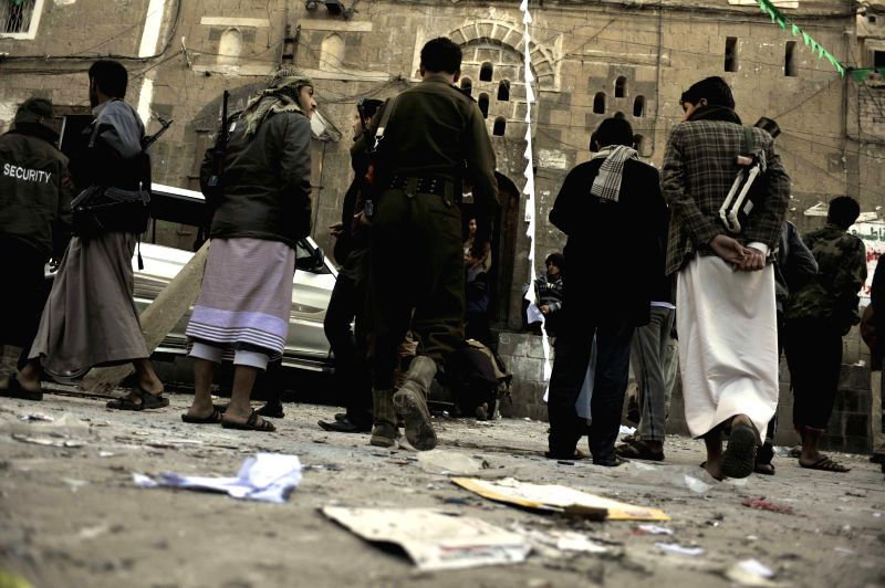 Civilians and Houthi militants gather at the explosion site in Sanaa, Yemen, on Dec. 23, 2014. One Houthi member was killed and two others injured in a series of ...