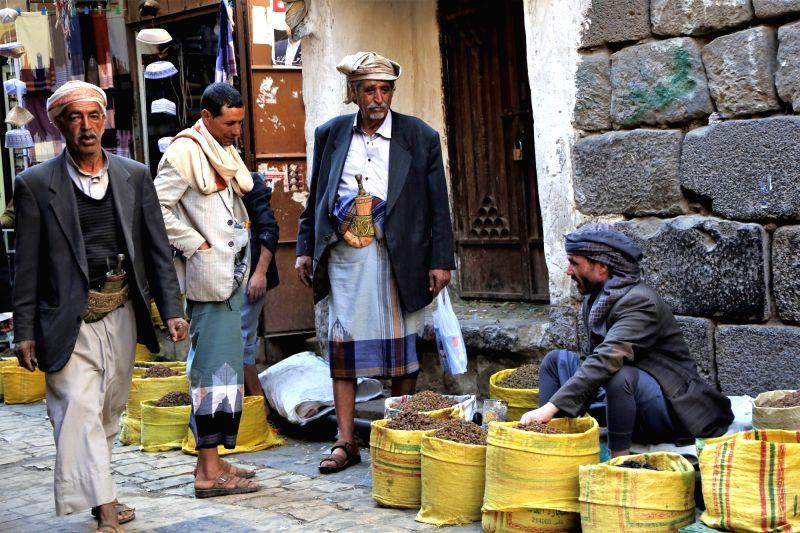 SANAA, Dec. 6, 2018 - People stand by a raisins vendor in Sanaa, Yemen, on Dec. 6, 2018.