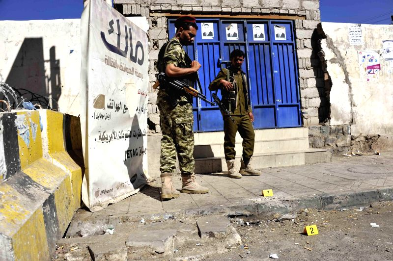Houthi fighters guard the gate of the republican palace where a bomb went off and wounded three people, in Sanaa, Yemen, on Feb. 7, 2015. The Shiite Houthi group held