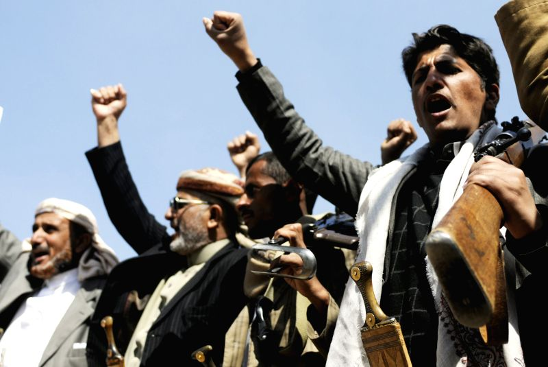 Shiite Houthi fighters shout slogans during clashes with presidential guards near the presidentail palace in Sanaa, Yemen, on Jan. 19, 2015.