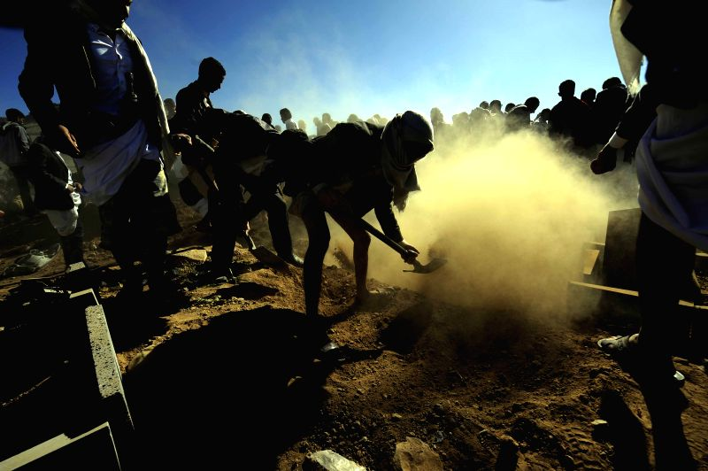 People dig graves for victims of a car bomb attack against the police academy in the grave during a funeral procession in Sanaa, Yemen, on Jan. 9, 2015. At least 37 ...