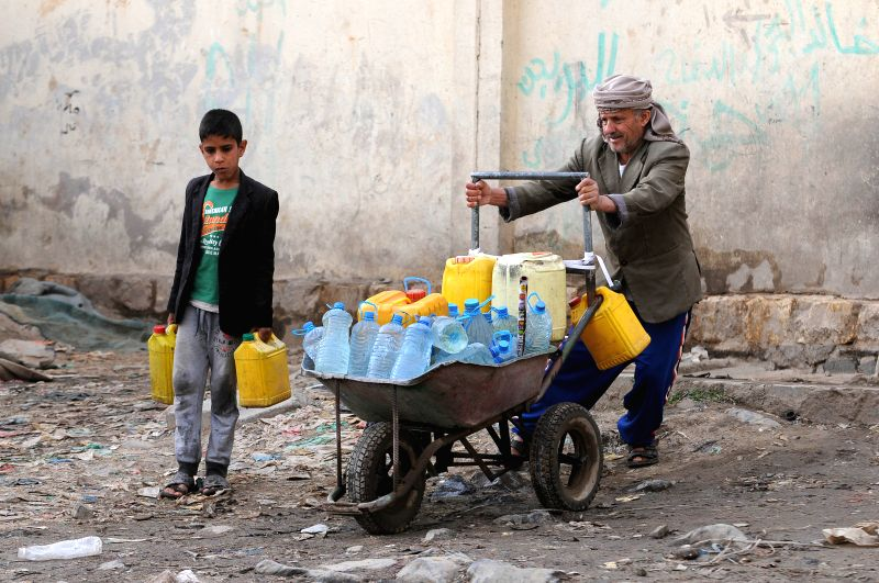 SANAA, July 24, 2018 - A boy walks beside his father returning home after they collected clean water from a free water pump during a clean running water crisis in Sanaa, Yemen, on July 24, 2018. ...