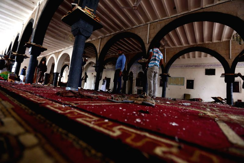 People clean the mosque that was attacked by Friday suicide bombings in Sanaa, Yemen, on March 23, 2015. The Yemeni people held a funeral for those who were killed ...