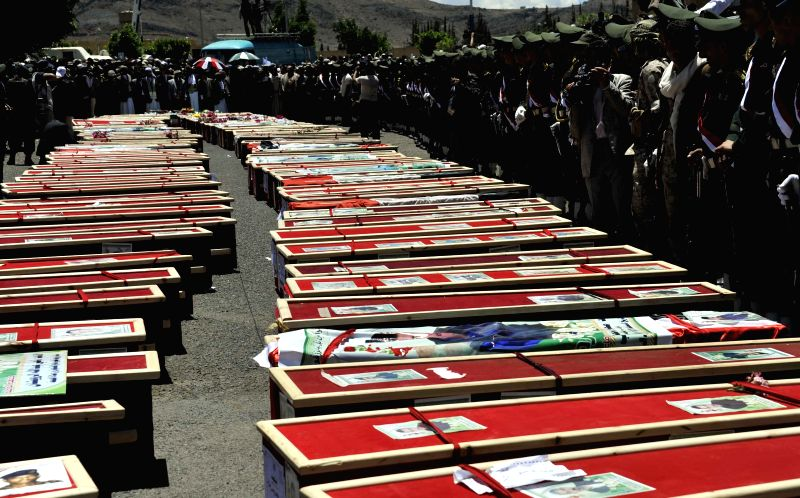 Honor guards stand around the coffins of the victims of suicide bombings during a funeral in Sanaa, Yemen, on March 25, 2015. The Yemeni people held a funeral for ...