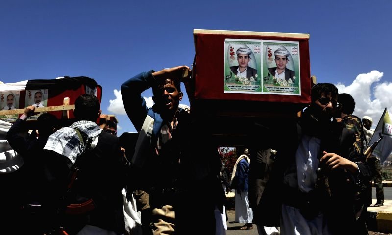 People carry the coffins of the victims of suicide bombings during a funeral in Sanaa, Yemen, on March 25, 2015. The Yemeni people held a funeral for victims of ...