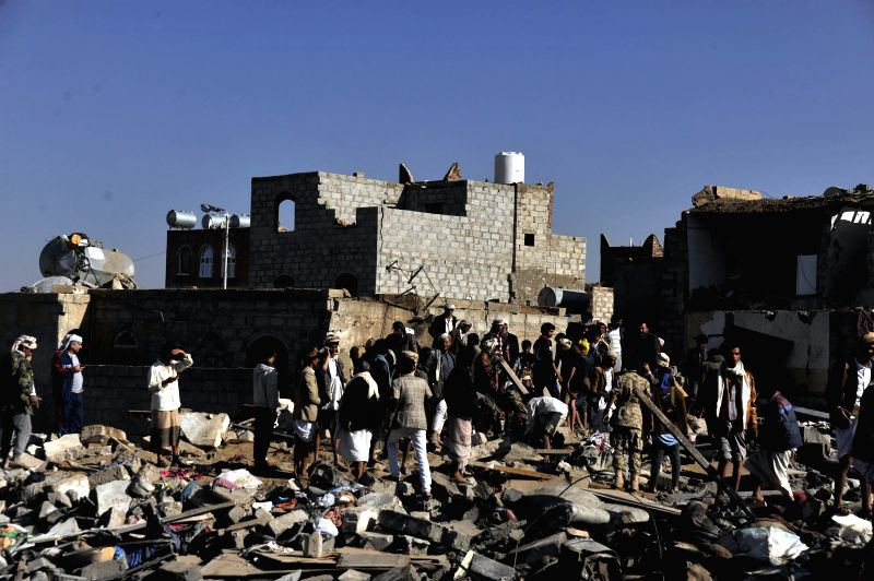 People gather at the bombed site near an air force base to search for causualties in Sanaa, Yemen, on March 26, 2015. Saudi Arabia and fellow Gulf Cooperation ...