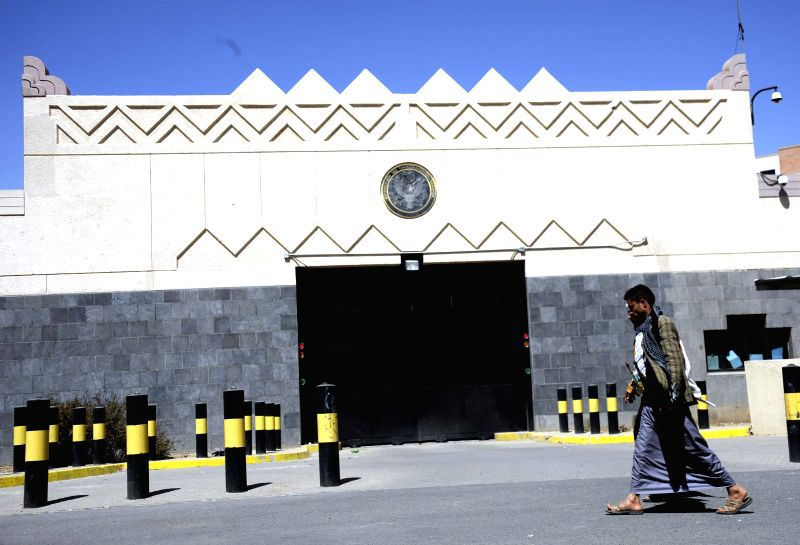 Yemenis walk past the U.S. embassy as the Yemeni authorities ordered to remove barriers, which were set up in front of the embassy after it was closed in early ...