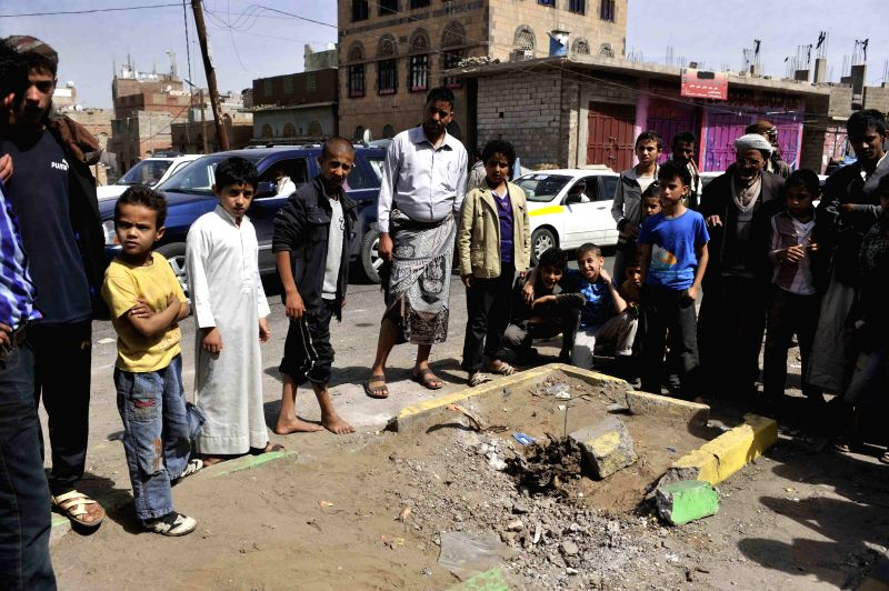 People check the blast site in Sanaa, Yemen, on May 9, 2014. A bomb blast targeted a military vechile carrying Yemeni soldiers to checkpoints near the U.S. and British .