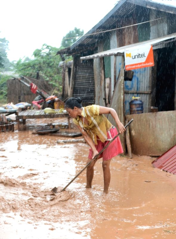 SANAMXAY (LAOS), July 27, 2018 A villager clears silt after an under-construction dam collapsed in Sanamxay District, Attapeu Province, Laos, on July 27, 2018. Six people were confirmed ...