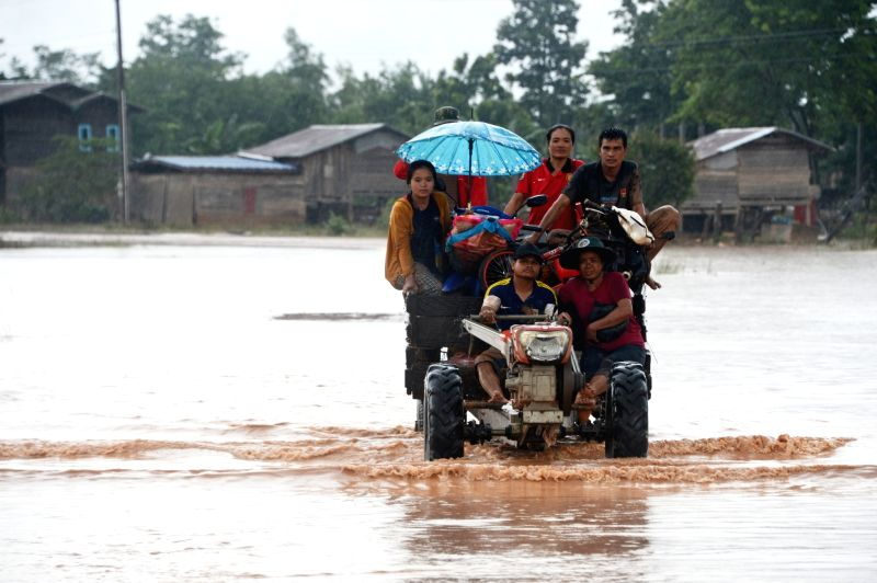 SANAMXAY (LAOS), July 27, 2018 Villagers are seen on a tractor after an under-construction dam collapsed in Sanamxay District, Attapeu Province, Laos, on July 27, 2018. Six people were ...