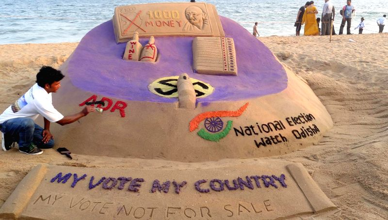 Sand artist Sudam Pradhan gives final touches to a sand sculpture appealing people to vote during the 2014 Lok Sabha Elections at Puri beach on April 15, 2014. - Sudam Pradhan