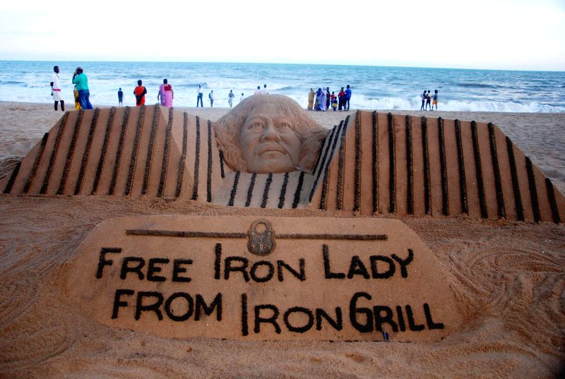 Sand artist Sudarsan Pattnaik created a sand sculpture of Irom Sharmila with a message `Free the Iron Lady from the Iron grill` at Puri beach of Odisha on Aug. 23, 2014. - Sudarsan Pattnaik