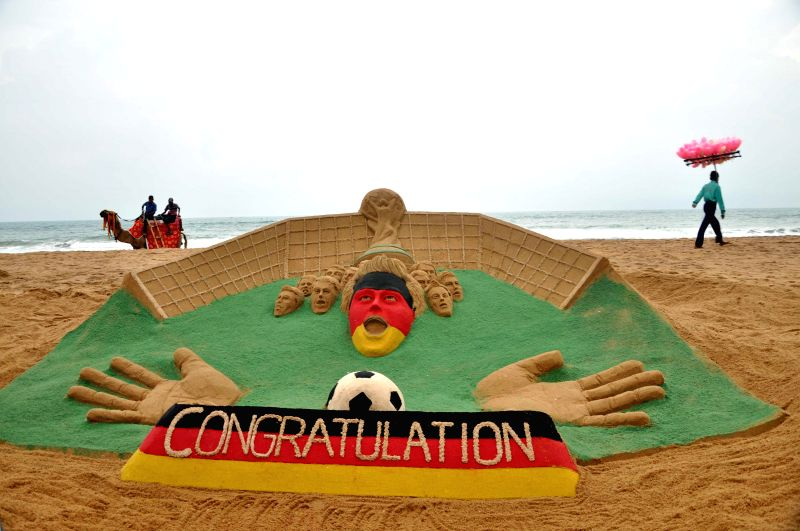 Sand artist Sudarsan Pattnaik's creation congratulating Germany after it won FIFA World Cup 2014 at Odisha's Puri beach on July 14, 2014.