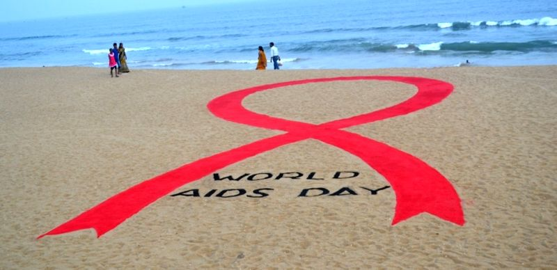 Sand artist Sudarsan Pattnaik who has created a sand ribbon ahead of the World AIDS Day on Puri beach on Nov 30, 2015.