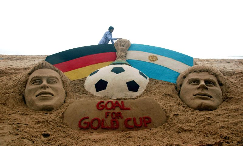 Sand artist Sudarsan Pattnaik with his creation depicting a clash between Germany and Argentina during FIFA WORLD CUP-2014 finals at Puri beach in Odisha on July 12, 2014.