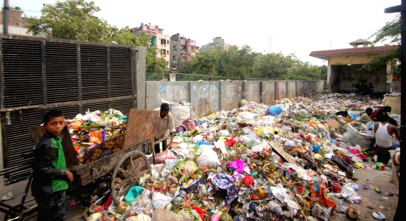 Sanitation workers busy working at a garbage vat in New Delhi, on Oct 27, 2015.