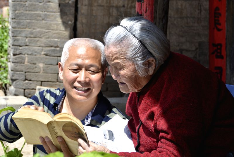 SANMENXIA, April 23, 2017 - The 95-year-old Wei Zuhe (R) and his 59-year-old son read a book in Qianqiu Village of Yima City, central China's Henan Province, April 23, 2017. The World Book Day falls ...