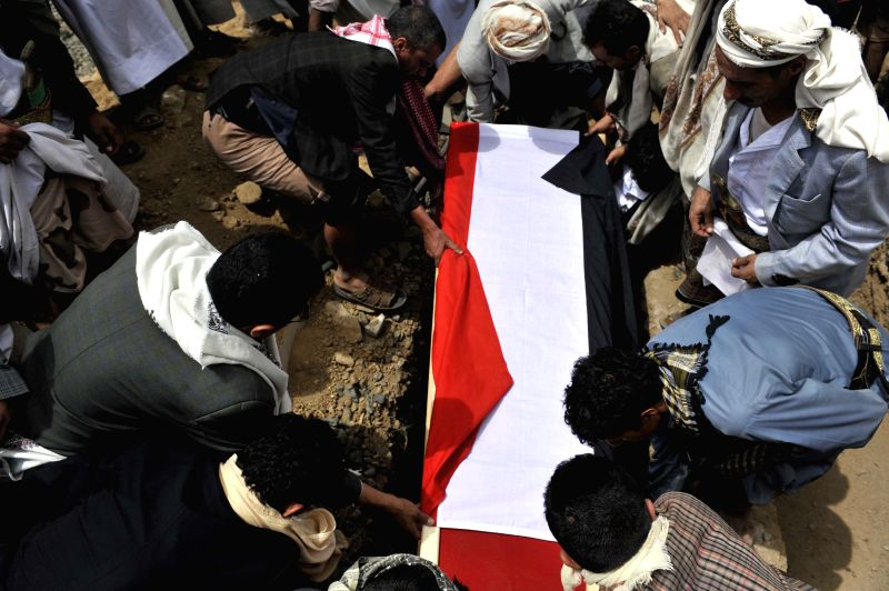 Yemenis bury a coffin of the soldier who was killed in the fighting with Shiite Houthi rebels in the northern Amran province during a funeral procession in Sanaa, ...