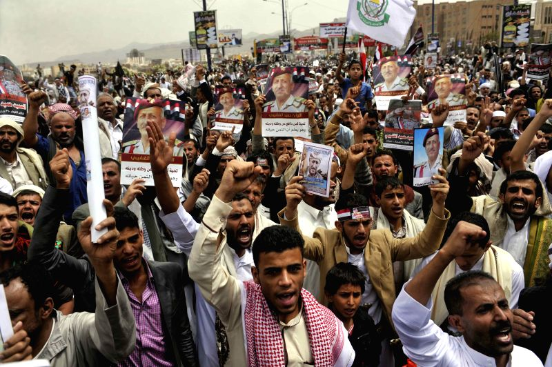 Yemeni people hold pictures of Hamid Alakeshaiba, commander of the 310 Brigade who was killed in clashes with the Shiite Houthi rebels, during a rally in Sanaa, ...