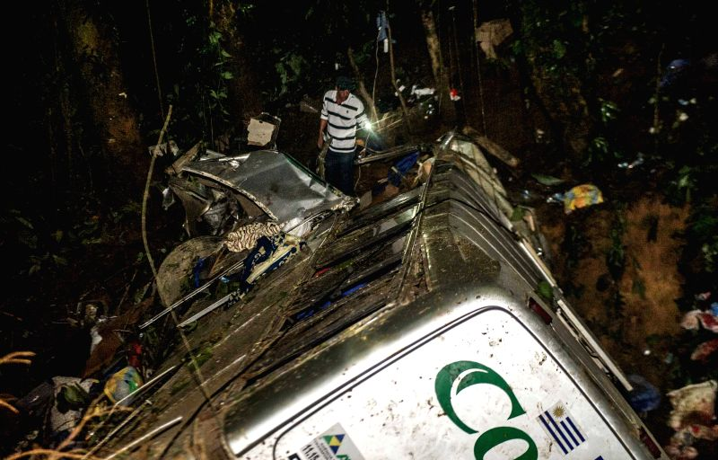 A man searches for the bodies at the site where a tourist bus plunged into a ravine in the state of Santa Catarina, Brazil, on March 15, 2015. At least 49 ...