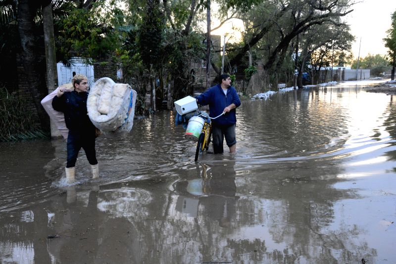 People walk through a flooded street, in Santa Fe, Argentina, on July 15, 2014.