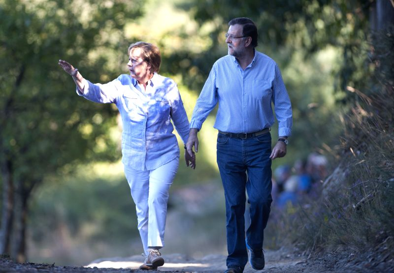 German Chancellor Angela Merkel (L) and Spanish Prime Minister Mariano Rajoy walk on the Way of Saint James, next to the village of Pedrouzo, some 10 km from ...