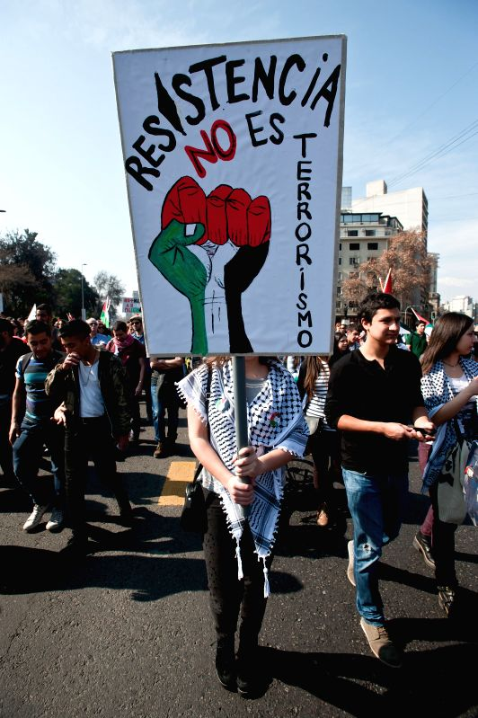 A Palestinian woman living in Chile holds a banner with slogans during a demonstration against Israeli offensive on the Gaza Strip, in Santiago, Chile, on Aug. 9, ..