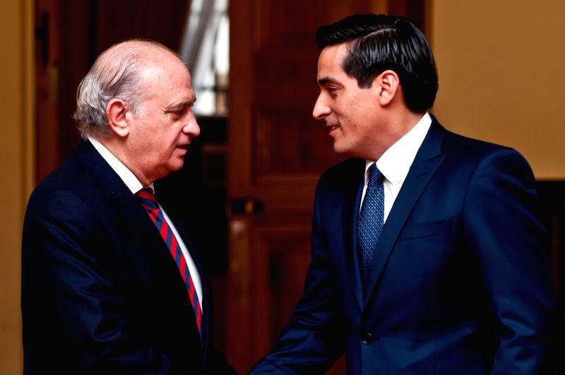 Chile's Interior Minister Rodrigo Penailillo (R) shakes hands with Spain's Interior Minister Jorge Fernandez Diaz (L) in Moneda Palace, Santiago, capital of Chile, on Dec. 15, 2014. Jorge .. - Rodrigo Penailillo