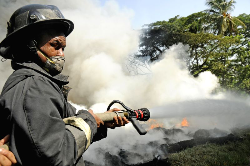 A fire fighter tries to extinguish a fire at a tire pile, located in La Herradura sector of Santiago city, north of Dominican Republic, on July 2, 2014. Tens of ...