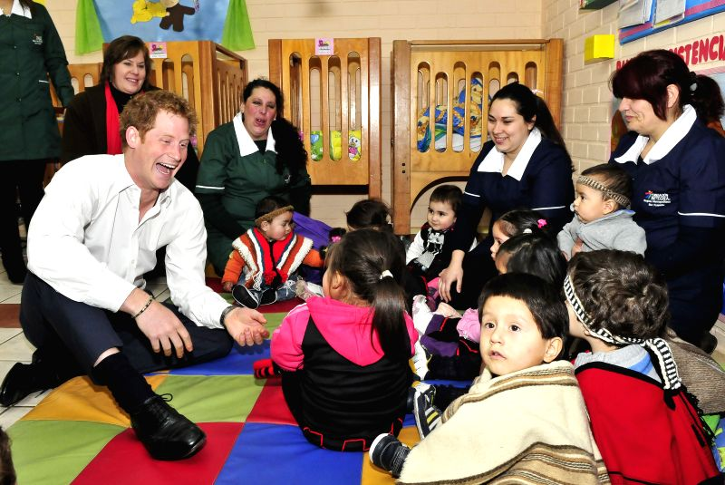 Image provided by the British Embassy to Chile shows British Prince Harry playing with children during a visit to the Children's Garden of the Integra Foundation ..